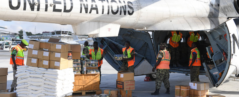 Soldiers serving under the African Union Mission in Somalia (AMISOM) load food supplies onto a UN supplies helicopter at Aden Abdulle Airport, Mogadishu